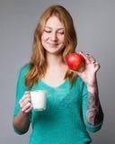 Portret van een jonge gemberdame in turkooise blouse met een kop o Royalty-vrije Stock Afbeelding