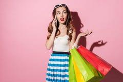 Portret van een jonge glimlachende vrouw die kleurrijke het winkelen zakken houden royalty-vrije stock afbeeldingen