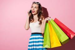 Portret van een jonge glimlachende vrouw die kleurrijke het winkelen zakken houden stock afbeelding