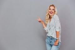 Portret van een jonge glimlachende vrouw die vredesteken tonen Royalty-vrije Stock Foto's