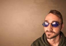 Portret van een jonge grappige mens met zonnebril en copyspace Stock Fotografie