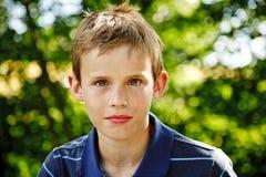 Portret van een jonge jongenszitting in de tuin Stock Afbeeldingen