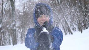 Portret van een jonge kerel die hand met sneeuw in het de winterbos slaan stock videobeelden