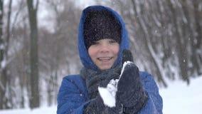 Portret van een jonge kerel die hand met sneeuw in het de winterbos slaan stock video