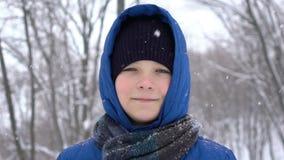 Portret van een jonge kerel in het de winterbos, sneeuwdalingen stock videobeelden