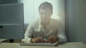 Portret van een jonge knappe beambte die op een draadloos toetsenbord typen stock footage