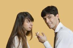Portret van een jonge man met sigaret terwijl vrouw die hem over gekleurde achtergrond bekijken Royalty-vrije Stock Fotografie