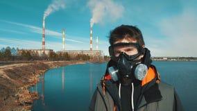 Portret van een jonge mens in een ademhalingsapparaat of een gasmasker Op de achtergrond komt de rook uit de pijpen van hydro-ele stock videobeelden