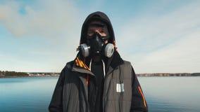 Portret van een jonge mens in een ademhalingsapparaat of een gasmasker Op de achtergrond komt de rook uit de pijpen van hydro-ele stock footage