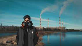 Portret van een jonge mens in een ademhalingsapparaat of een gasmasker Op de achtergrond komt de rook uit de pijpen van hydro-ele stock video