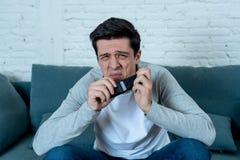 Portret van een jonge mens die doen schrikken en geschokte het letten op TV kijken Menselijke uitdrukkingen en emoties stock foto