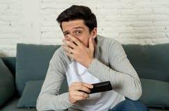 Portret van een jonge mens die doen schrikken en geschokte het letten op TV kijken Menselijke uitdrukkingen en emoties stock afbeeldingen