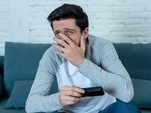 Portret van een jonge mens die doen schrikken en geschokte het letten op TV kijken Menselijke uitdrukkingen en emoties stock afbeelding