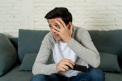 Portret van een jonge mens die doen schrikken en geschokte het letten op TV kijken Menselijke uitdrukkingen en emoties stock foto's