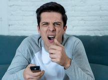 Portret van een jonge mens die doen schrikken en geschokte het letten op TV kijken Menselijke uitdrukkingen en emoties royalty-vrije stock foto