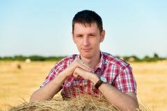 Portret van een jonge mens die op een baal van hooi leunt Royalty-vrije Stock Foto's