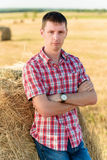 Portret van een jonge mens die op een baal van hooi leunt Royalty-vrije Stock Fotografie