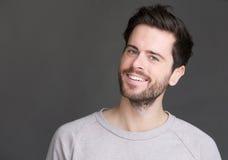 Portret van een jonge mens die op geïsoleerde grijze achtergrond glimlachen Royalty-vrije Stock Afbeelding