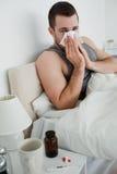 Portret van een jonge mens die zijn neus blaast Stock Afbeelding