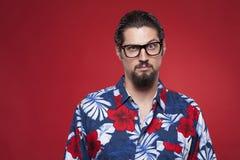 Portret van een jonge mens in Hawaiiaans overhemd met opgeheven wenkbrauw Stock Foto