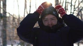 Portret van een jonge mens in een jasje die zijn kap nemen weg en de sneeuw weg van zijn winter GLB schudden Close-up stock video