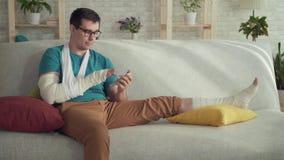 Portret van een jonge mens met een gebroken arm en beenzitting op een bank en het gebruiken van een smartphone stock videobeelden