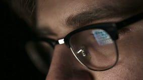 Portret van een jonge mens met glazen die bij nacht werkt Sluit omhoog stock videobeelden