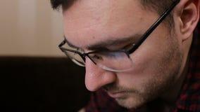 Portret van een jonge mens met glazen die met tablet werkt stock videobeelden
