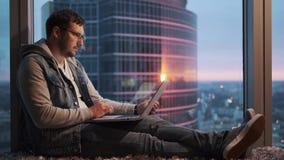 Portret van een jonge mensenzitting zorgvuldig achter laptop door een venster op een hoge vloer stock video