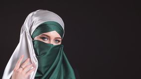 Portret van een jonge moderne Moslimvrouw in een hijab op zwarte achtergrond stock video