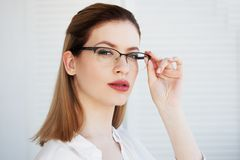 Portret van een jonge modieuze bedrijfsvrouw in een wit overhemd en glazen stock afbeeldingen