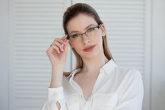 Portret van een jonge modieuze bedrijfsvrouw in een wit overhemd en glazen royalty-vrije stock foto's