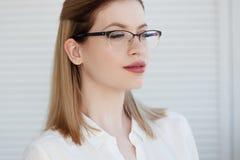 Portret van een jonge modieuze bedrijfsvrouw in een wit overhemd en glazen royalty-vrije stock afbeeldingen