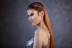 Portret van een jonge modieuze vrouw met gouden metaalwenkbrauwen Futurisme, manier van de toekomst royalty-vrije stock afbeelding