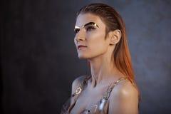 Portret van een jonge modieuze vrouw met gouden metaalwenkbrauwen Futurisme, manier van de toekomst royalty-vrije stock foto