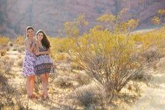 Portret van een jonge moeder en haar dochter in woestijn van Rode Roc Stock Afbeeldingen