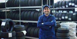 Portret van een jonge mooie autowerktuigkundige in een autoworkshop, op de achtergrond van de dienst Concept: reparatie van machi Stock Foto
