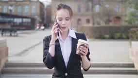 Portret van een jonge mooie bedrijfsstudente die in een kostuum, rond de stad, het drinken koffie lopen, die op spreken stock videobeelden