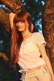 Portret van een jonge mooie roodharige vrouw in appelboomgaard stock foto's