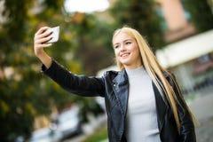 Portret van een jonge mooie studente videovraag die, selfie, een telefoon houden stock fotografie