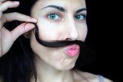 Portret van een jonge mooie vrouw die met donker haar een bundel van haar haar over haar hogere lip houden royalty-vrije stock foto's