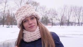 Portret van een jonge mooie vrouw in het park van de de winterstad dat de camera terwijl correct haar lang haar en wit bekijkt stock video