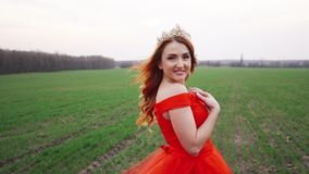 Portret van een jonge mooie vrouw in een rode kleding tegen een aardachtergrond stock video