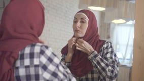 Portret van een jonge moslimvrouw die een sjaal voor een spiegel dragen royalty-vrije stock afbeeldingen