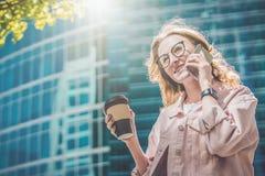 Portret van een jonge onderneemster het drinken koffie en het spreken op haar celtelefoon Een meisje roept haar vrienden op de te Royalty-vrije Stock Afbeelding