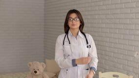 Portret van een jonge pediater arts in een kinderen` s kliniek stock video