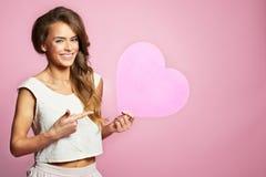 Portret van een jonge schoonheid, glimlachende vrouw met roze hart Royalty-vrije Stock Afbeeldingen