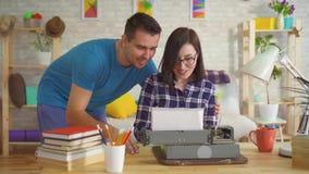 Portret van een jonge schrijver die op een oude schrijfmachine naast de jonge mens schrijven stock videobeelden