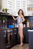 Portret van een jonge slanke vrouw in lingerie in de keuken Stock Foto's