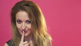 Portret van een jonge speelse vrouw die die stilte gebaar en knipogen tonen op de roze achtergrond wordt geïsoleerd stock video
